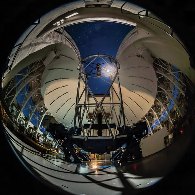 Gemini South telescope inside with a moonlit dome at night.